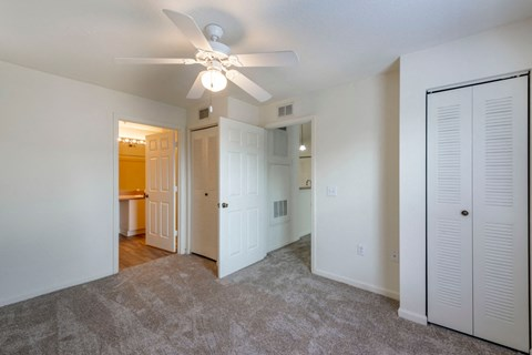 Carpeted Bedroom with White Ceiling Fan Sliding Closet and Door to Attached Bathroom