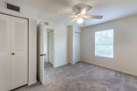 Carpeted Bedroom with Ceiling Fan Sliding Closet and Window