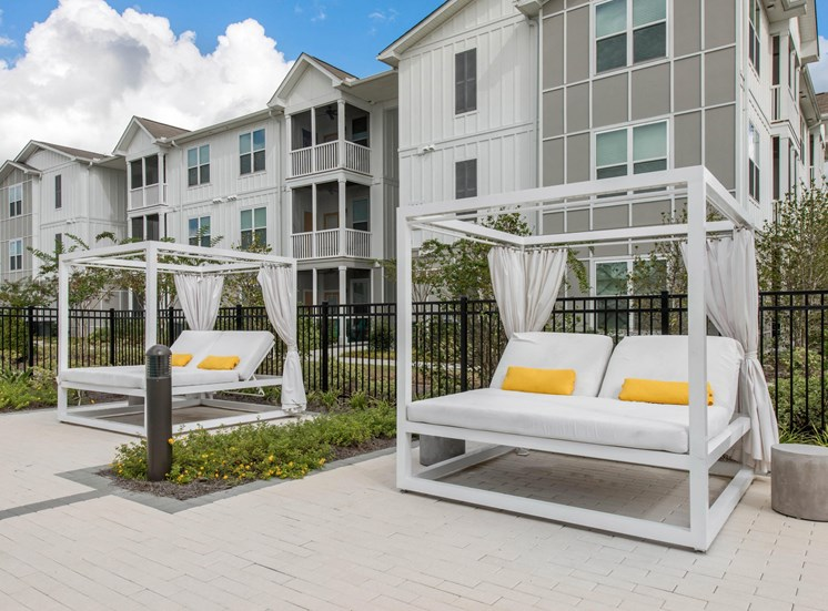 Poolside Lounge Seating in Front of Fence with Building in the Background
