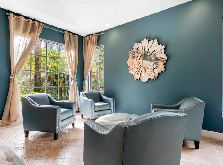 Clubhouse sitting area with large windows, four sitting chairs, coffee table, blue walls, peach curtains and decorative mirror