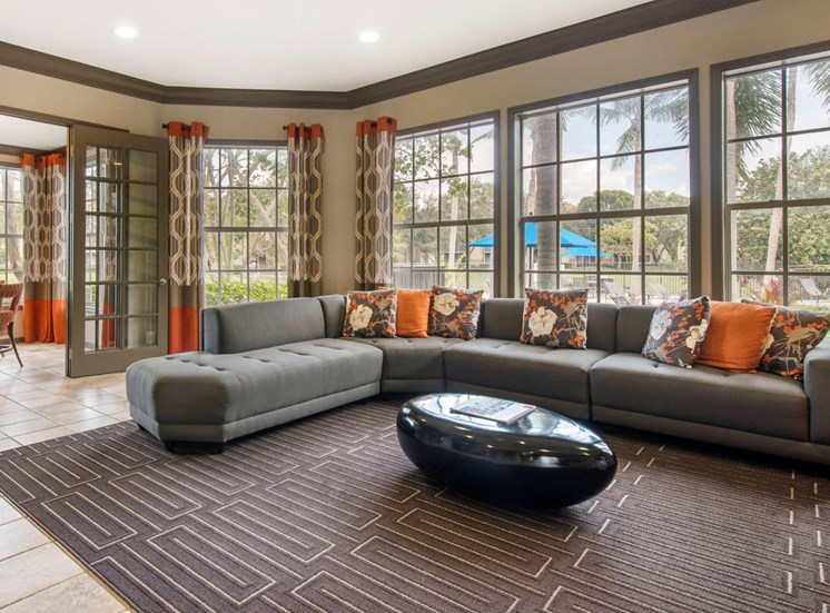 Clubhouse Seating Area with  Sectional Couch and Coffee Table in Front of Windows