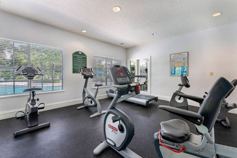 Cardio Fitness Studio interior with treadmill and stationary bikes facing window overlooking pool