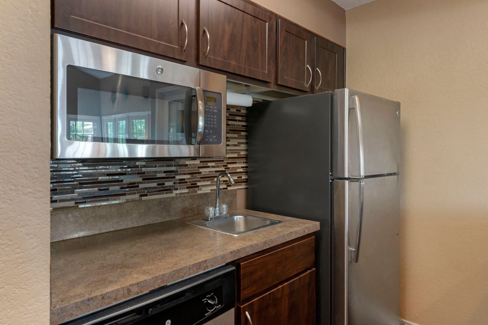 Clubhouse Kitchen with brushed nickel appliances, wooden cabinets, and microwave