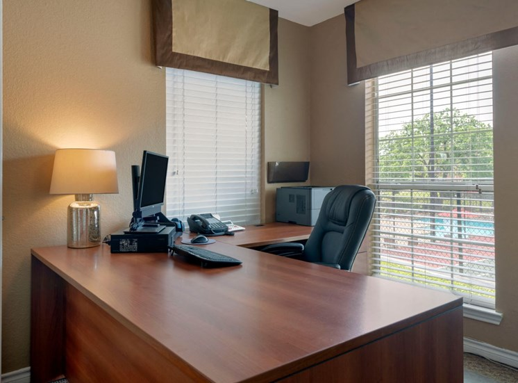 Leasing office and desk with a computer, phone, and leather chair