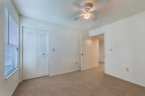 Vacant Bedroom with carpet, ceiling fan and light, bi-fold doors to closet, and window with mini blinds
