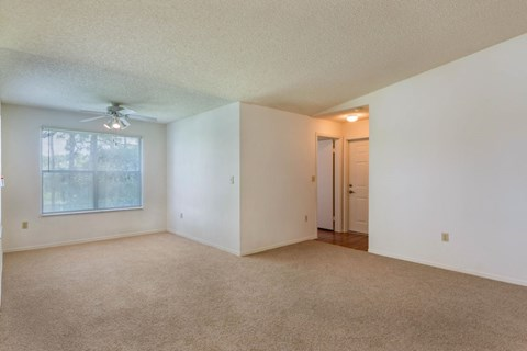Vacant Living Room large windows and mini blinds, ceiling fand with light, and carpeted flooring