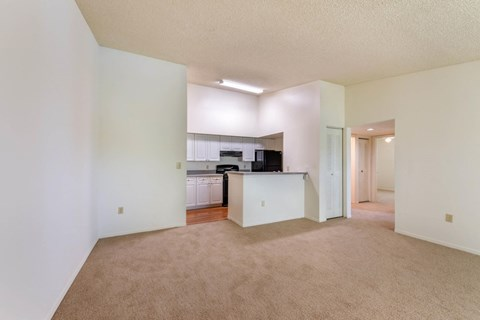 Vacant Apartment Image of Dining Area with beige carpetand Kitchen in the background