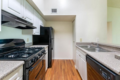 Apartment Kitchen with hardwood style floors, white cabinets, and black appliances