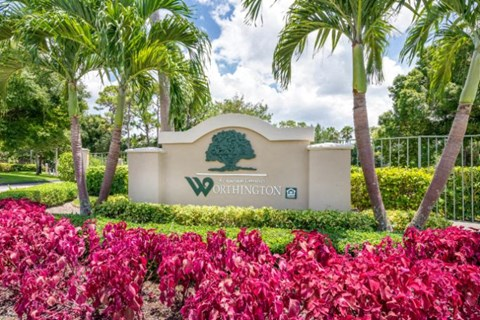 Worthington Apartments Entrance Sign with purple flowers and palm tree landscaping