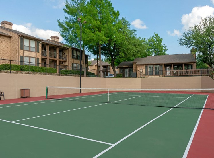 Tennis courts with lights and building exterior in the background