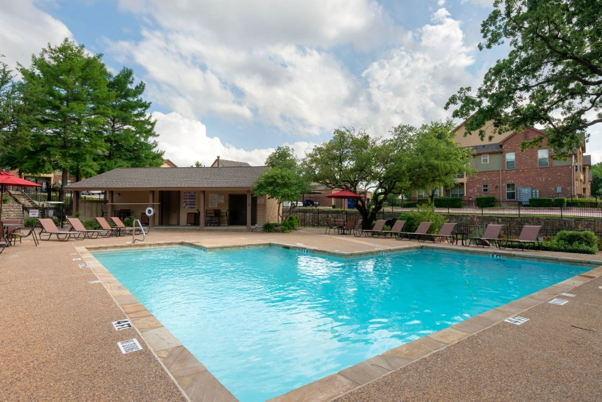 Swimming pool with tanning deck, blue skies, green trees, and clubhouse exterior in the background