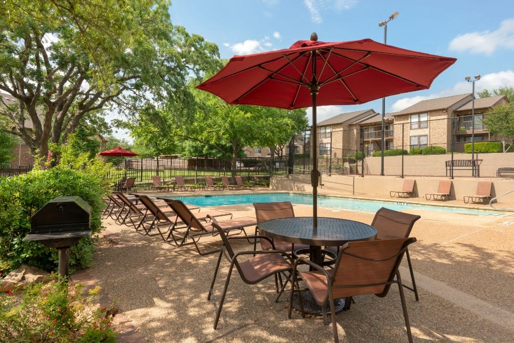 Swimming pool with red umbrella and picnic tables