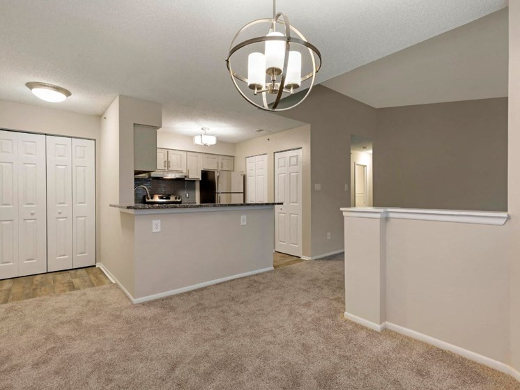 Carpeted Living Room Next to Kitchen with Breakfast Bar White Cabinets and Stainless Steel Appliances