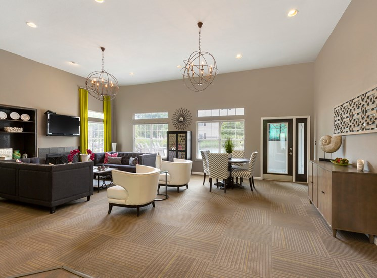 Clubhouse with Contemporary Fixtures and Decorations and Dining Table with Chevron Print Chairs Next to White Armchairs