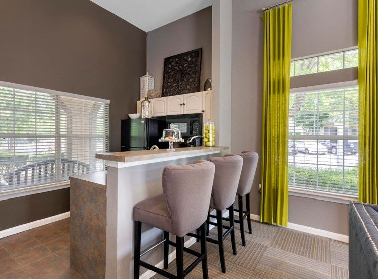 Clubhouse Kitchen with Breakfast Bar with Barstools Next to Large Windows with Lime Green Curtains