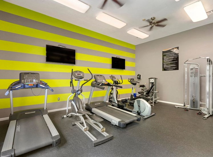 Fitness Center with Exercise Equipment and Mounted TVS on Lime Green and Grey Striped Wall
