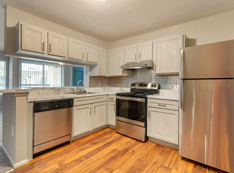 Updated Kitchen with Stainless Steel Appliances White Cabinets and White Marble Style Counters
