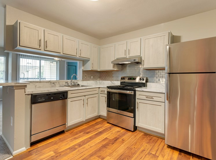 Premium Upgrade Kitchen with white countertops, white cabinets, stainless appliances, wood-style flooring, and pass-through bar to the living room