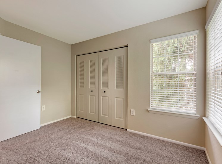 Carpeted bedroom with two toned paint, bifold doors to closet and two windows