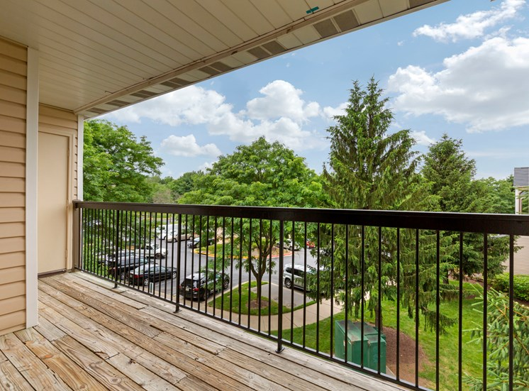 balcony with wood decking, black metal railing and storage looking out to grass area with mature trees
