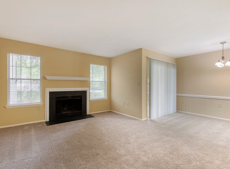 Carpeted living room with two-tone paint, fireplace and sliding door to patio