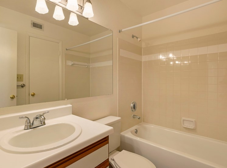 Bathroom with white counter, wood cabinets and full size bathtub