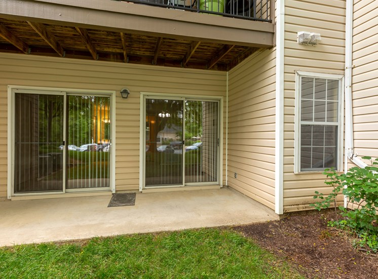 Exterior back patio with two sliding doors looking out over grass area.