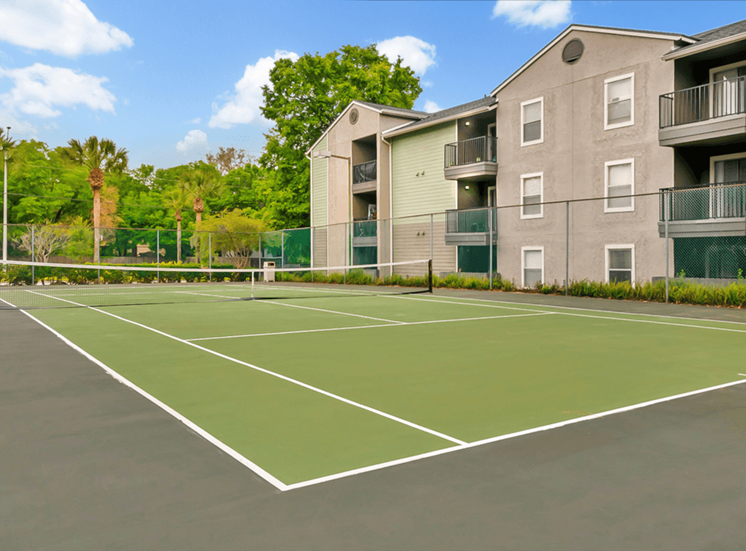 Outdoor tennis court surrounded by native landscaping and apartment building exterior in the background