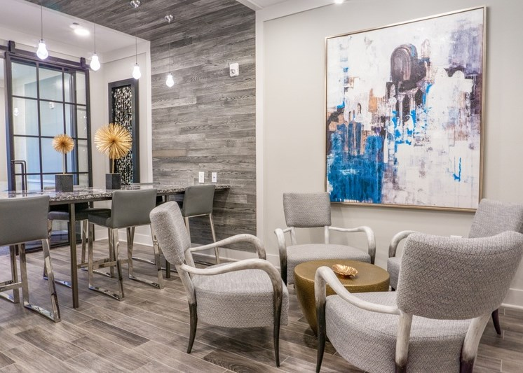 Clubhouse interior with white and gray color scheme, large art decor on the walls, and modern light fixtures