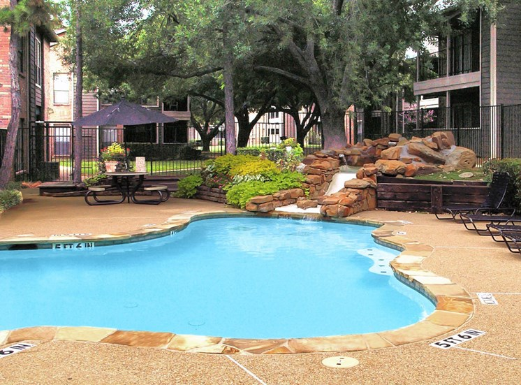 Swimming pool with stone waterfall surrounded by sundeck, green landscaping, picnic table with umbrella and building exteriors in the background