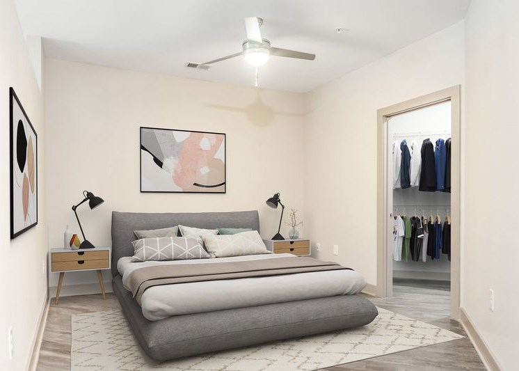 Furnished bedroom with gray and white color scheme, ceiling fan, and walk-in closet