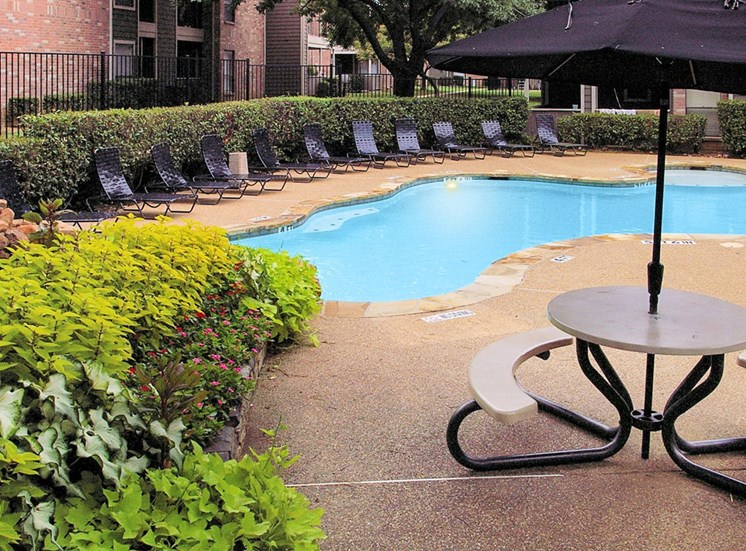 Swimming pool with lounge seating, picnic table with umbrella and building exteriors