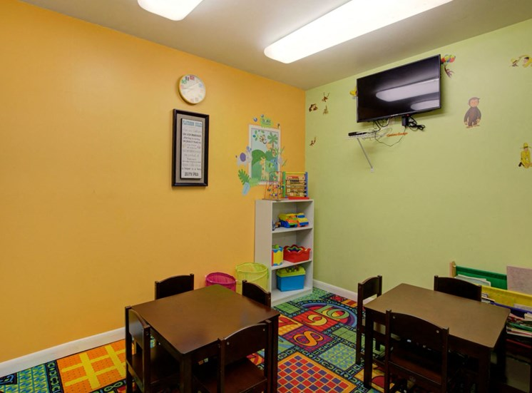 Colorful Activity Room with Small Tables and Mounted TV