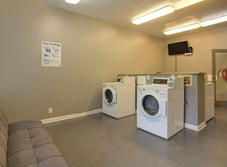 Clothes Care Center with Machines a Grey Couch and a Mounted TV