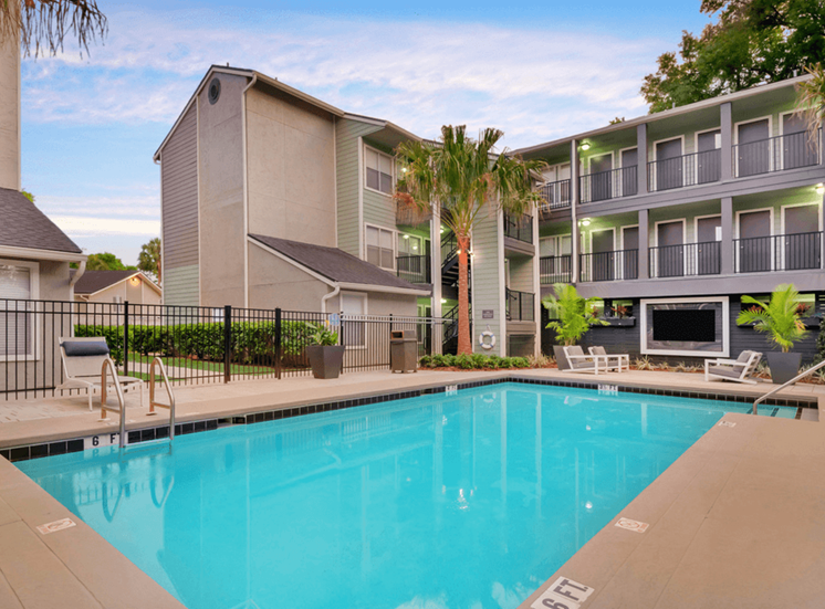 Swimming pool with palm tree and apartment building exterior in the background