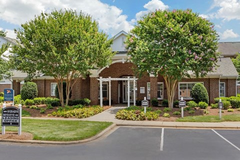 Exterior leasing office entrance with lush landscaping, trees and flowers