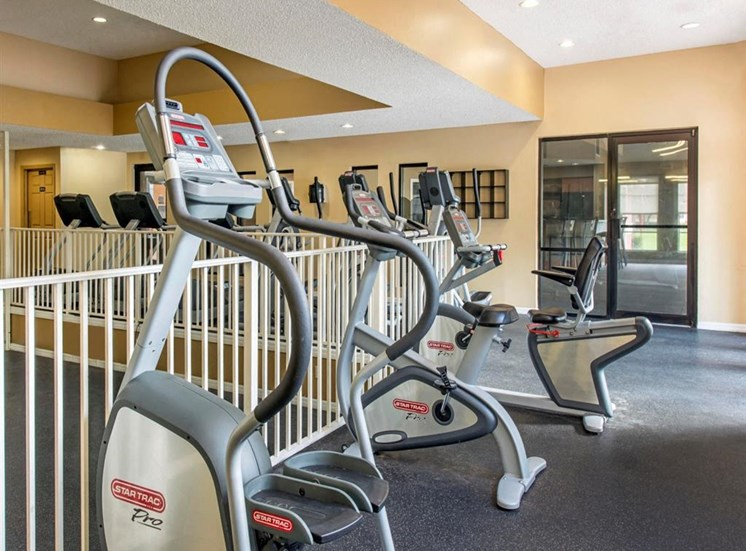 Fitness Center with Cardio Equipment Along Railing in Front of Racquetball Court