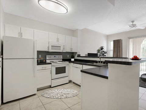 The Preserve at Deer Creek Apartments |  Fully Equipped Kitchen with White Appliances and Tile Flooring