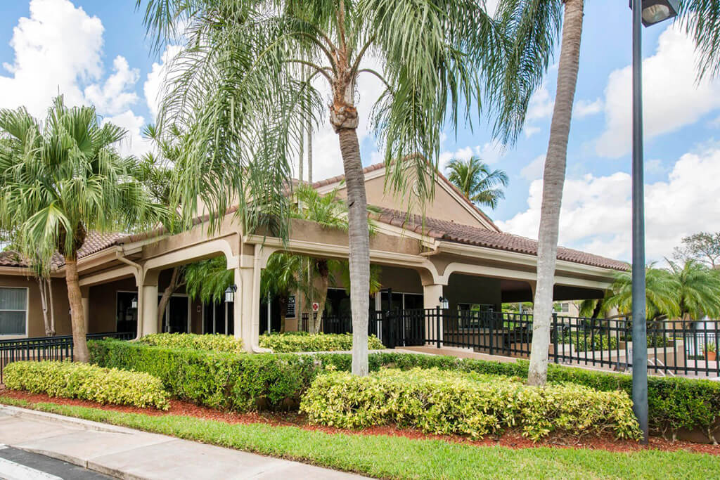 Leasing office exterior with palm trees