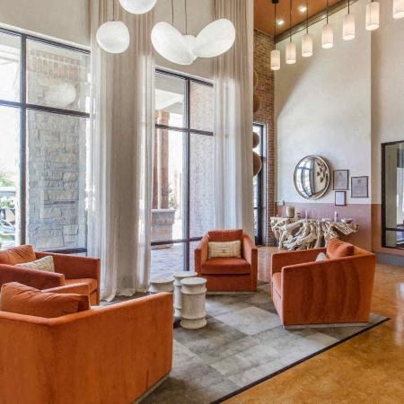 Clubhouse interior with modern lights, orange accent chairs, hardwood style floors, and a gray accent rug