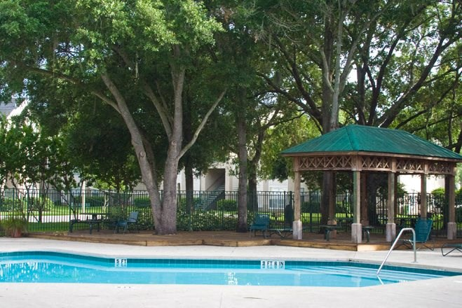 Fenced in Swimming Pool and Sun Deck with Lounge Chairs with a Pavilion Near Treeline