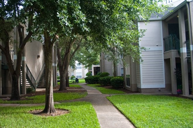 Shaded Walkway Between Buildings with Trees and Shrubs Throughout