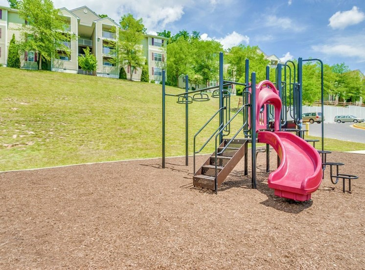 Playground For Children on wood chips and Apartment buildings in the background
