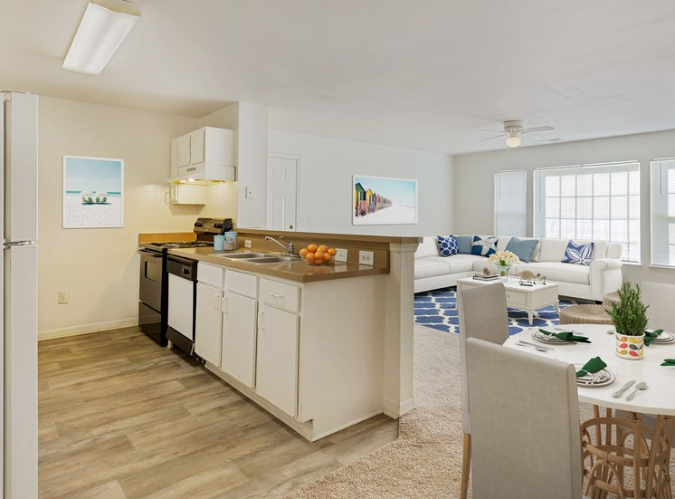 Virtual rending of kitchen and living with white couches, blue accents, and large windows
