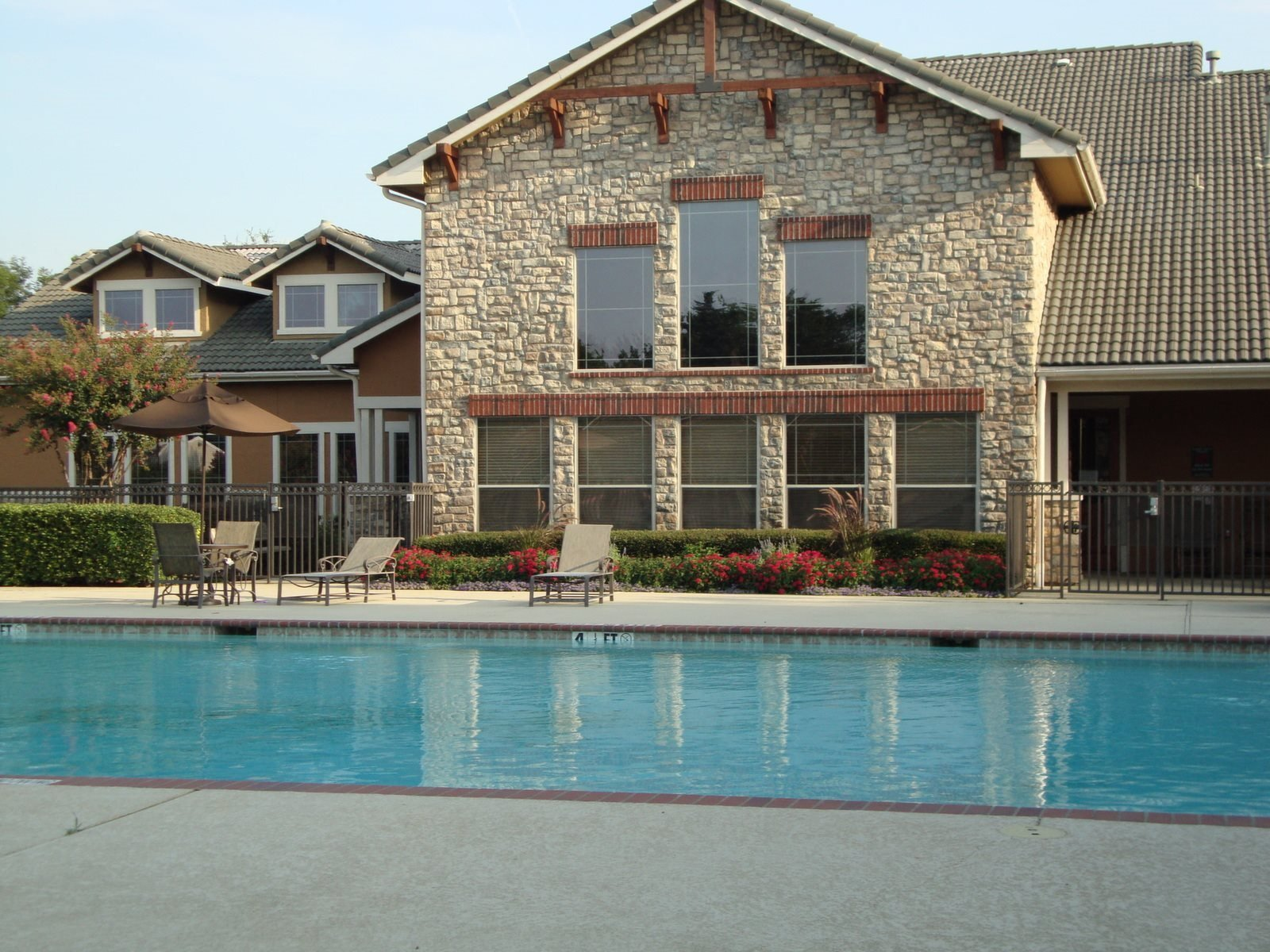 Building exterior with swimming pool, tanning deck, and clubhouse exterior