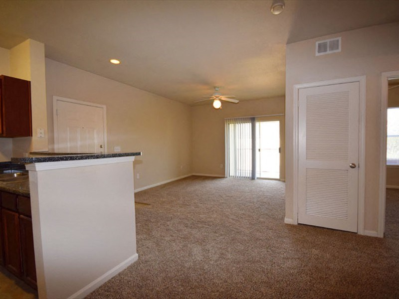 Living room with wall to wall carpet and balcony