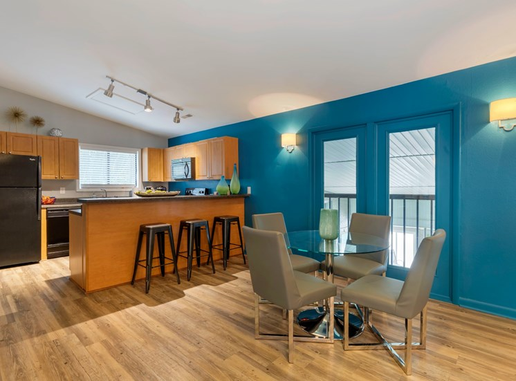 Clubhouse Kitchen with Black Appliances Blonde Cabinets BLue Accent Wall and Dining Table