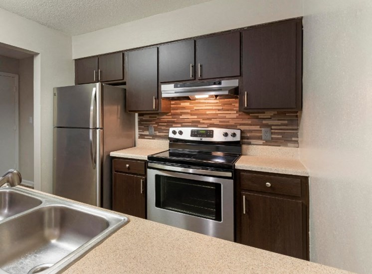 Kitchen with Brown Cabinets Stainless Steel Appliances and Beige Counters with Stone Backsplash