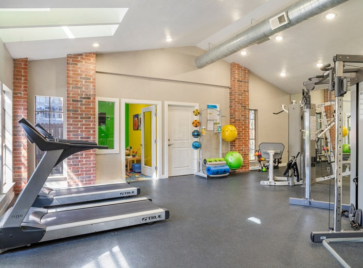 Bright Fitness Center with Exercise Equipment with Colorful Playroom Attached