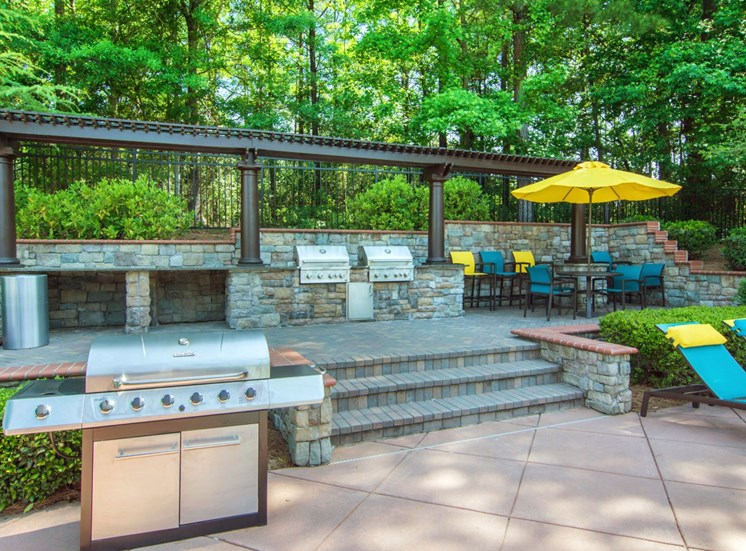 Summer Kitchen on Brick Platform Behind Grill with Blue and Yellow Chairs